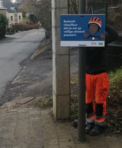 Medewerker plaatst bord fietsveiligheidscampagne met tekst: Bedankt chauffeur dat je me op veilige afstand passeert
