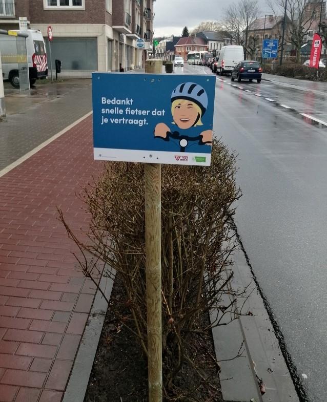 Bord fietsveiligheidscampagne met tekst: Bedankt snelle fietser dat je vertraagt